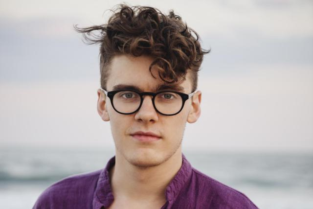 Young hipster guy with glasses at the beach